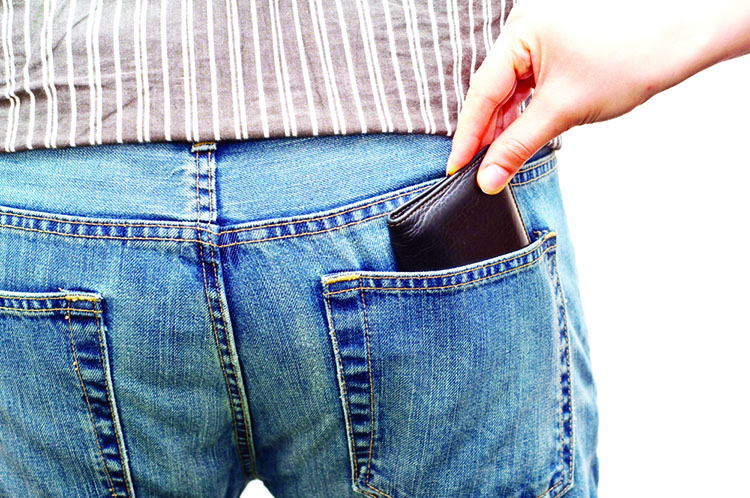 woman stealing a wallet from man's back pocket isolated