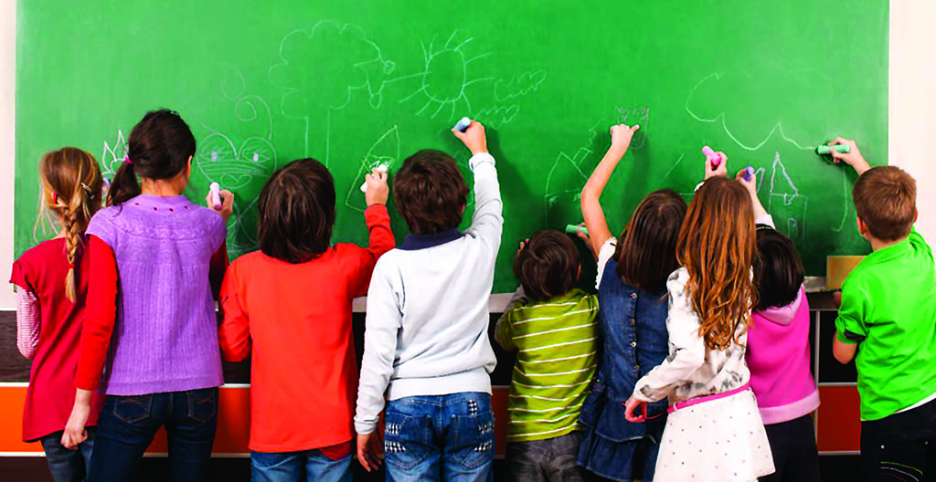 Group of nine children drawing on school chalkboard with chalks.