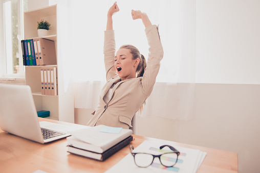 Tired businesswoman stretching and yawning after working day